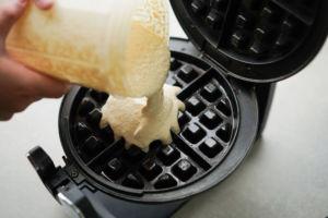pouring waffle batter into waffle iron