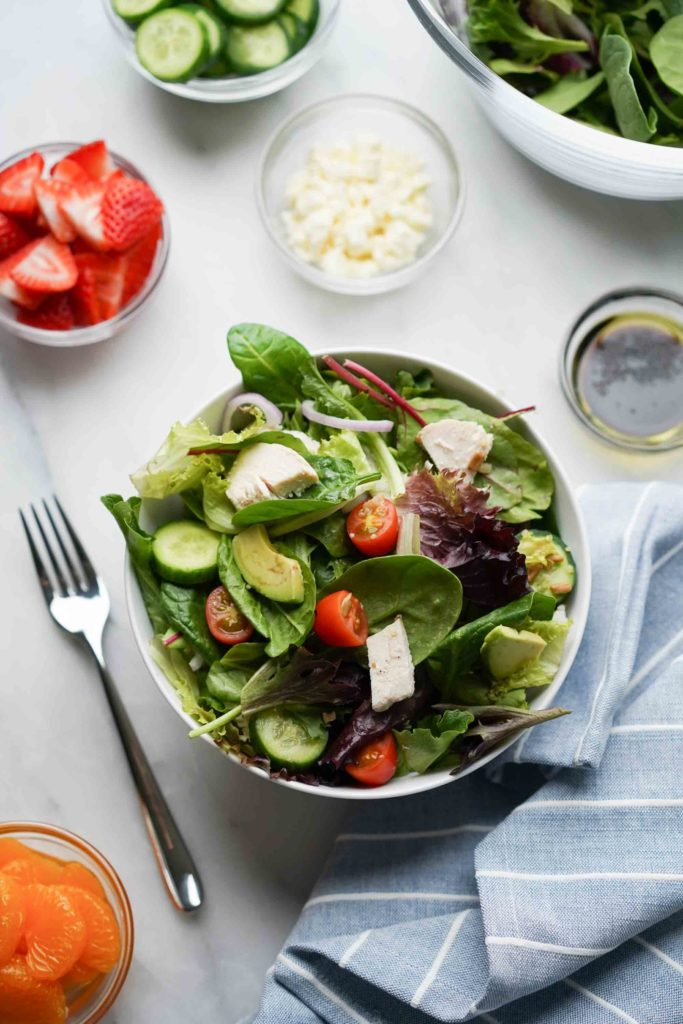 bowl of spinach and green salad with toppings