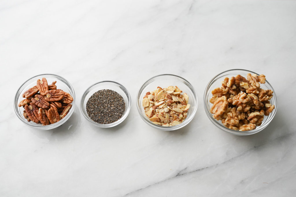 bowls of nuts and seeds: pecans, chia seeds, sliced almonds, walnuts