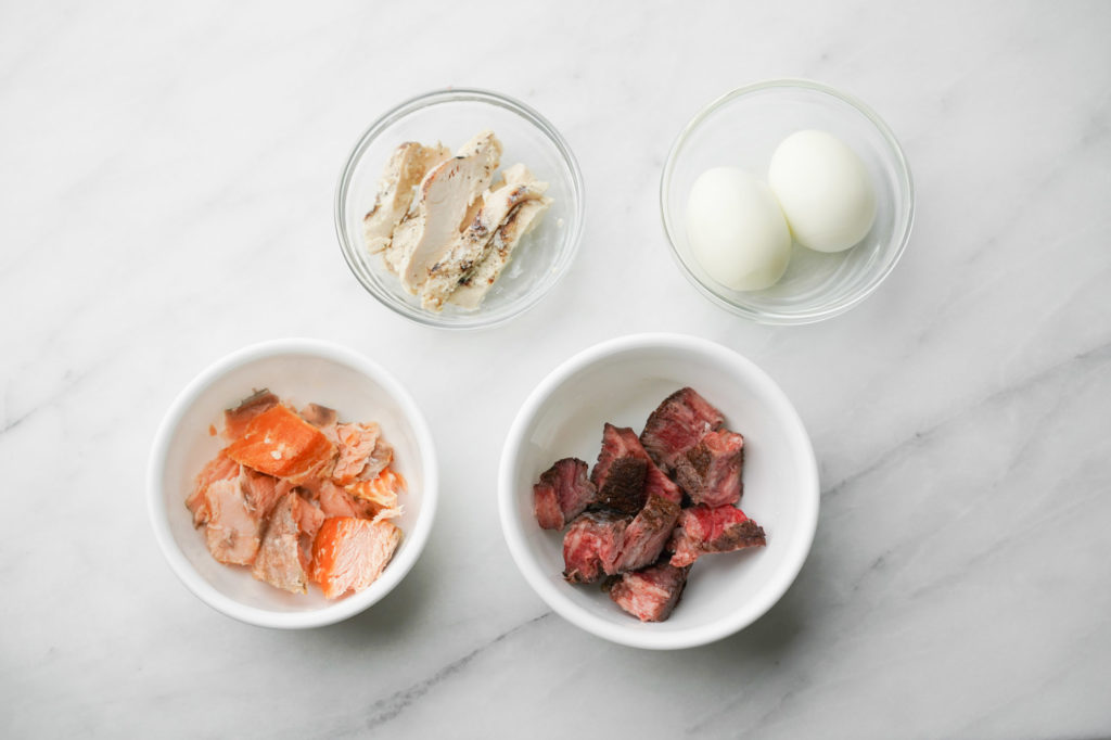 smoked salmon, chicken, steak, and boiled eggs in glass bowls
