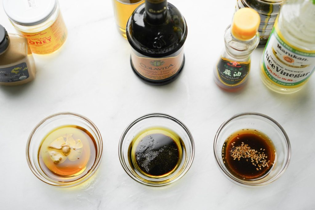 three salad dressings: honey mustard, balsamic and sesame