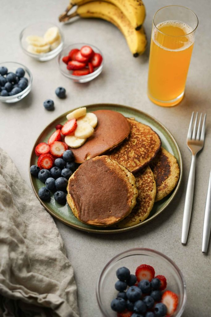 stack of banana protein pancakes with fruit
