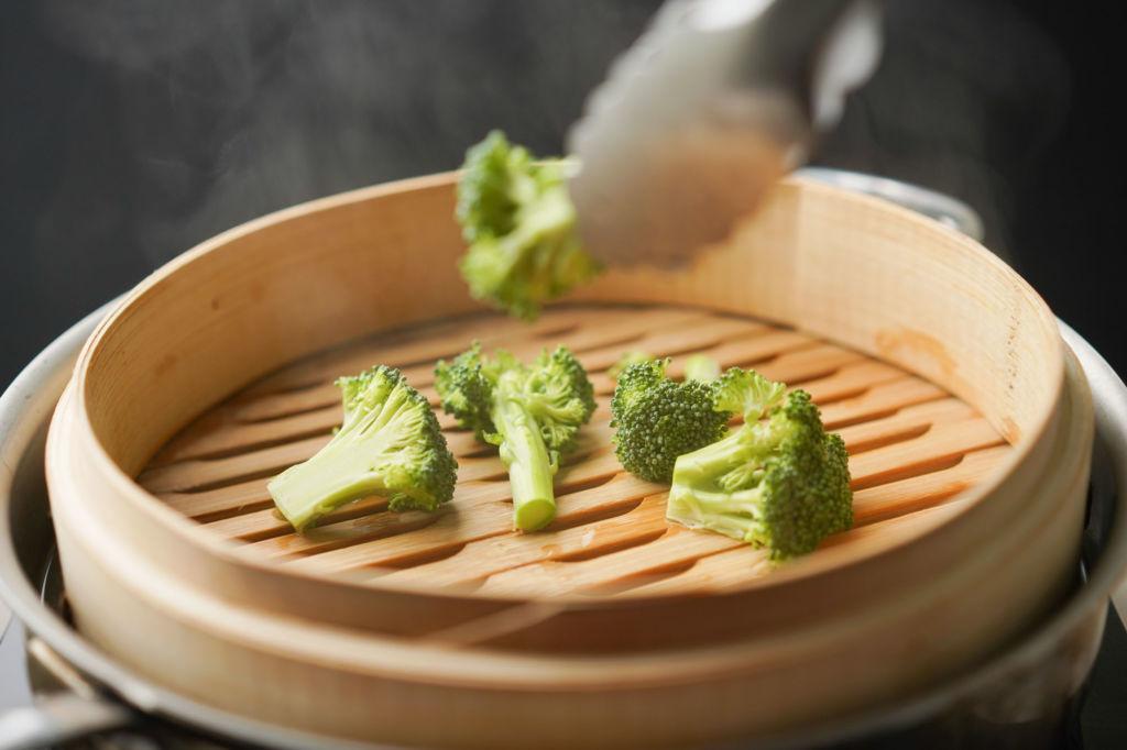 adding broccoli to steamer