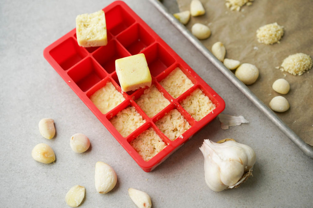 frozen garlic in ice cube tray and sheet pan