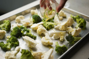 pouring oil onto sheet pan of broccoli and cauliflower