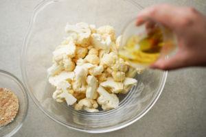 adding oil to cauliflower