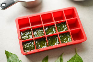 adding basil and oil into ice cube tray